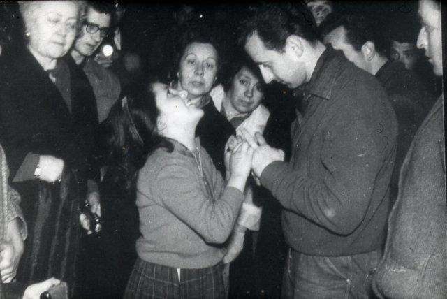 Mari Loli zieht einem Mann seinen Ehering an den Finger.