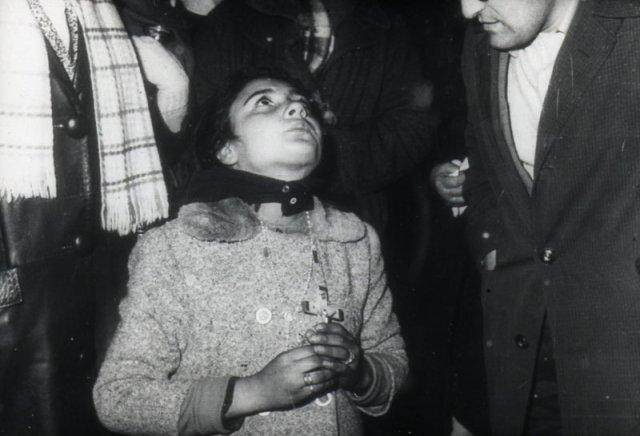 Conchita mit einem Kreuz in der Hand, laufend in Ekstase.